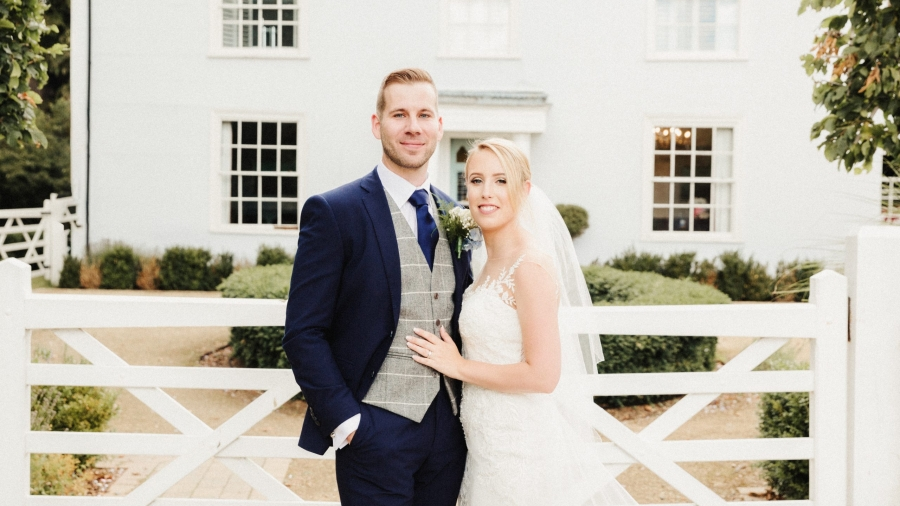 Bride and groom outside the white cottage