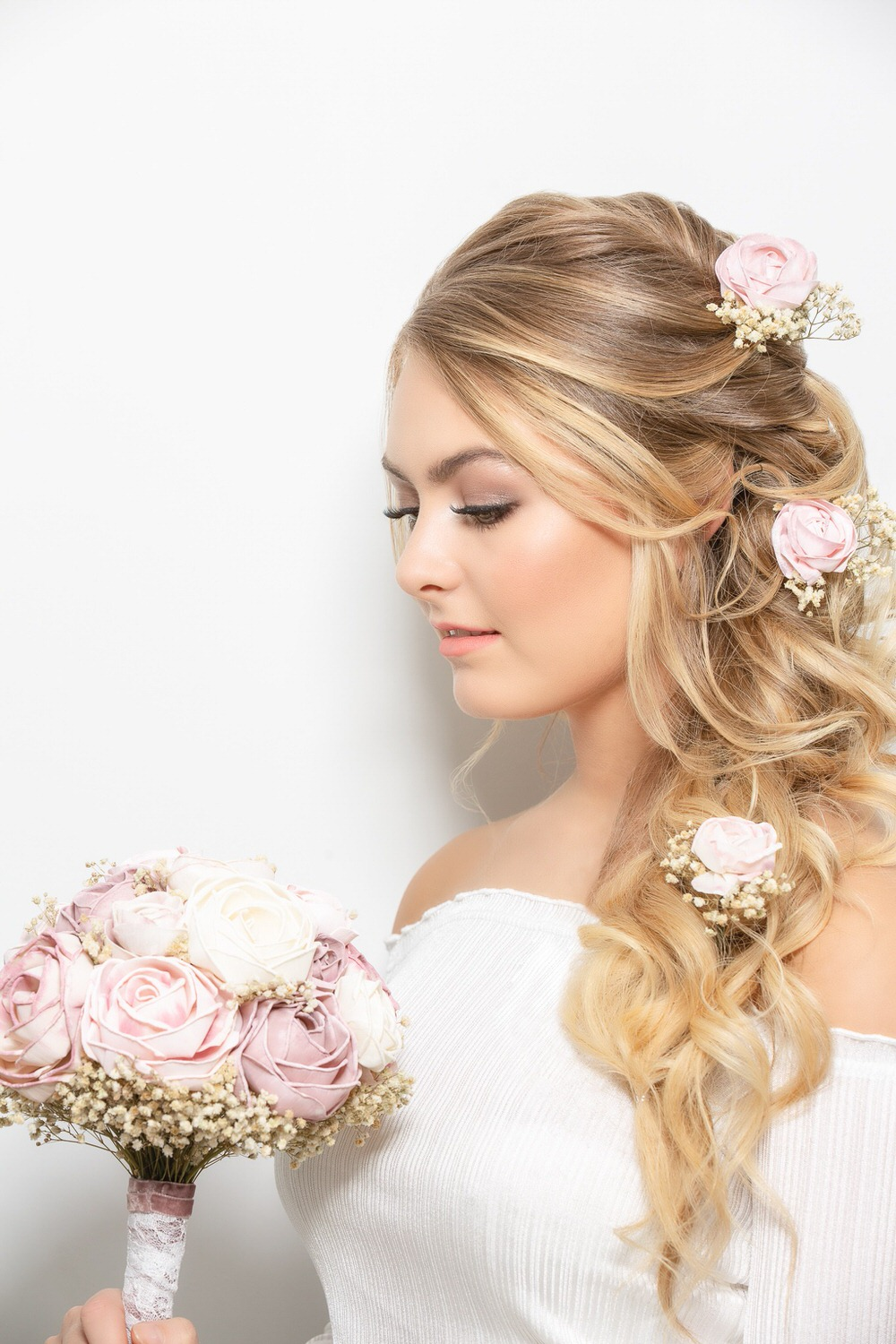 Blonde haired bride looking at her wedding bouquet