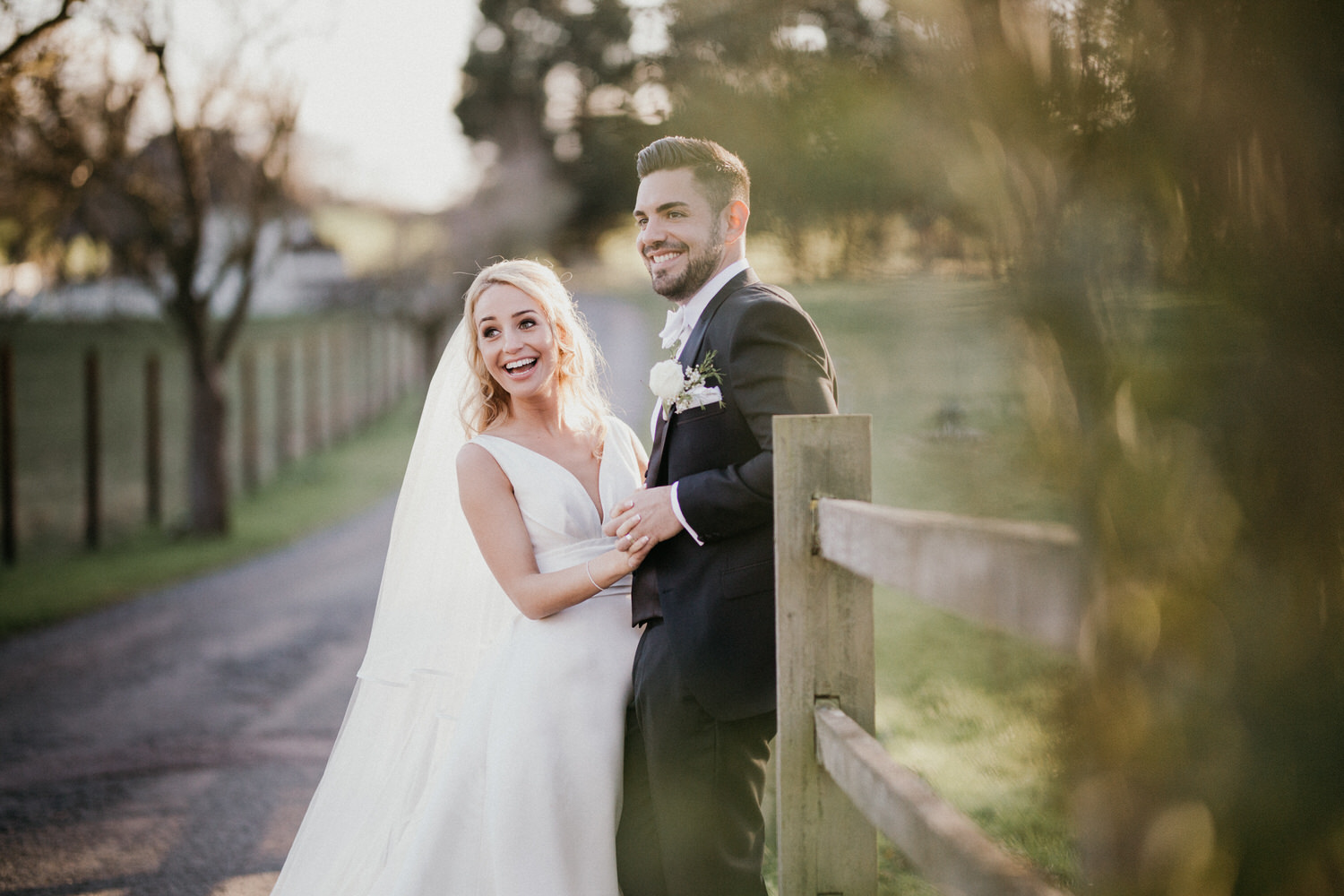 Bride and groom laughing holding hands outside during sunset