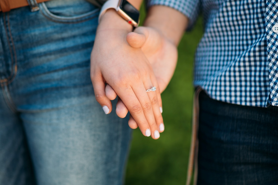 Close up shot of couple holding hands showing their engagement ring