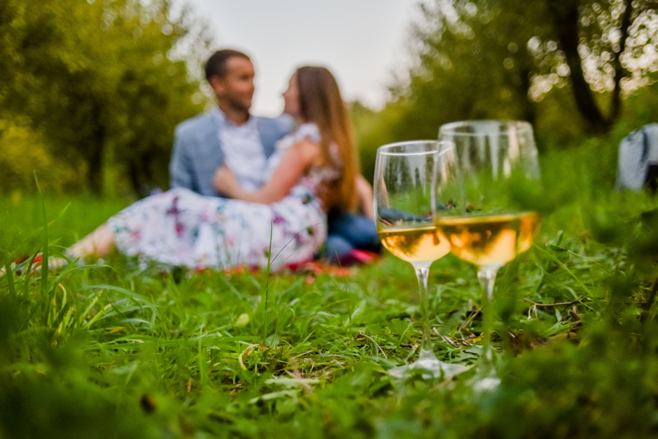 Couple sitting on a picnic blanket in the park with drinks in the foreground