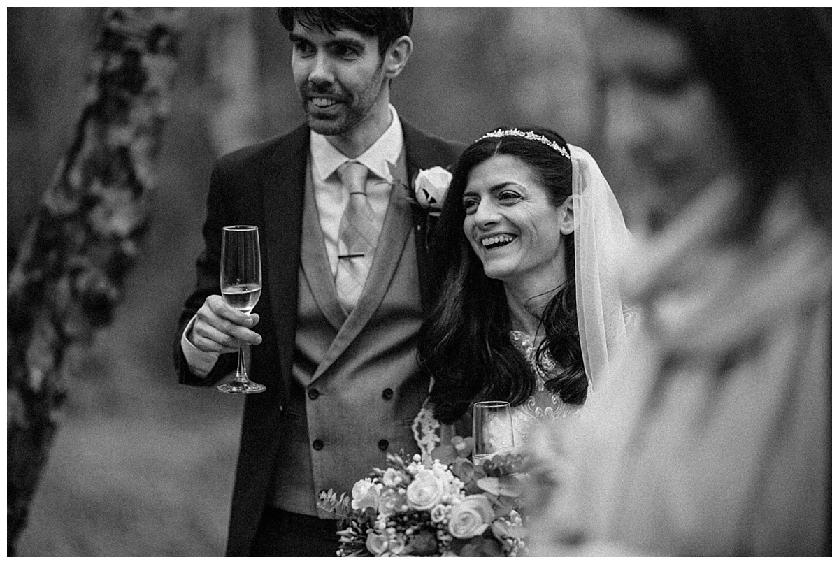 Black and white image of the bride and groom drinking and laughing