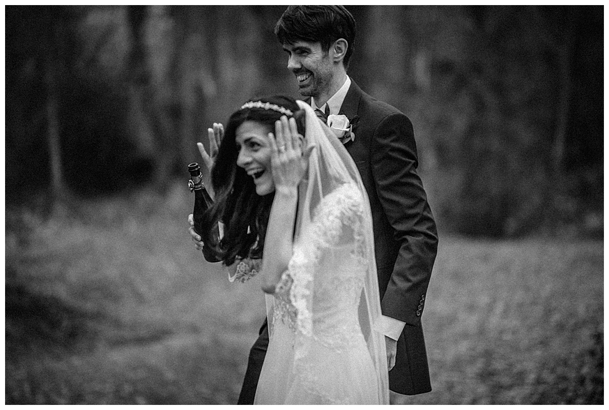 Black and white image of the bride and groom laughing