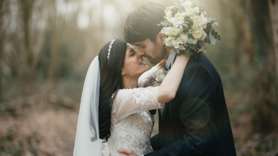 Bride and groom hold each other and kiss