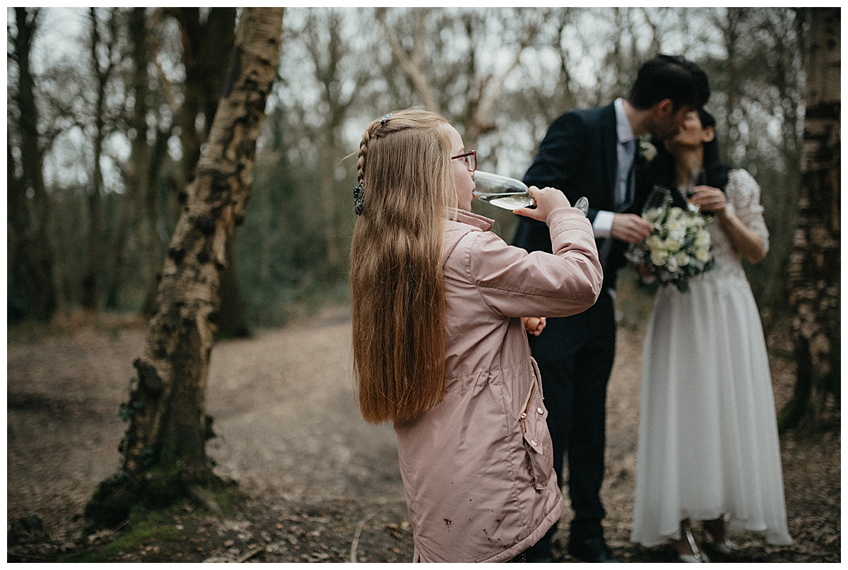Flower girl drinks as the bride and groom kiss