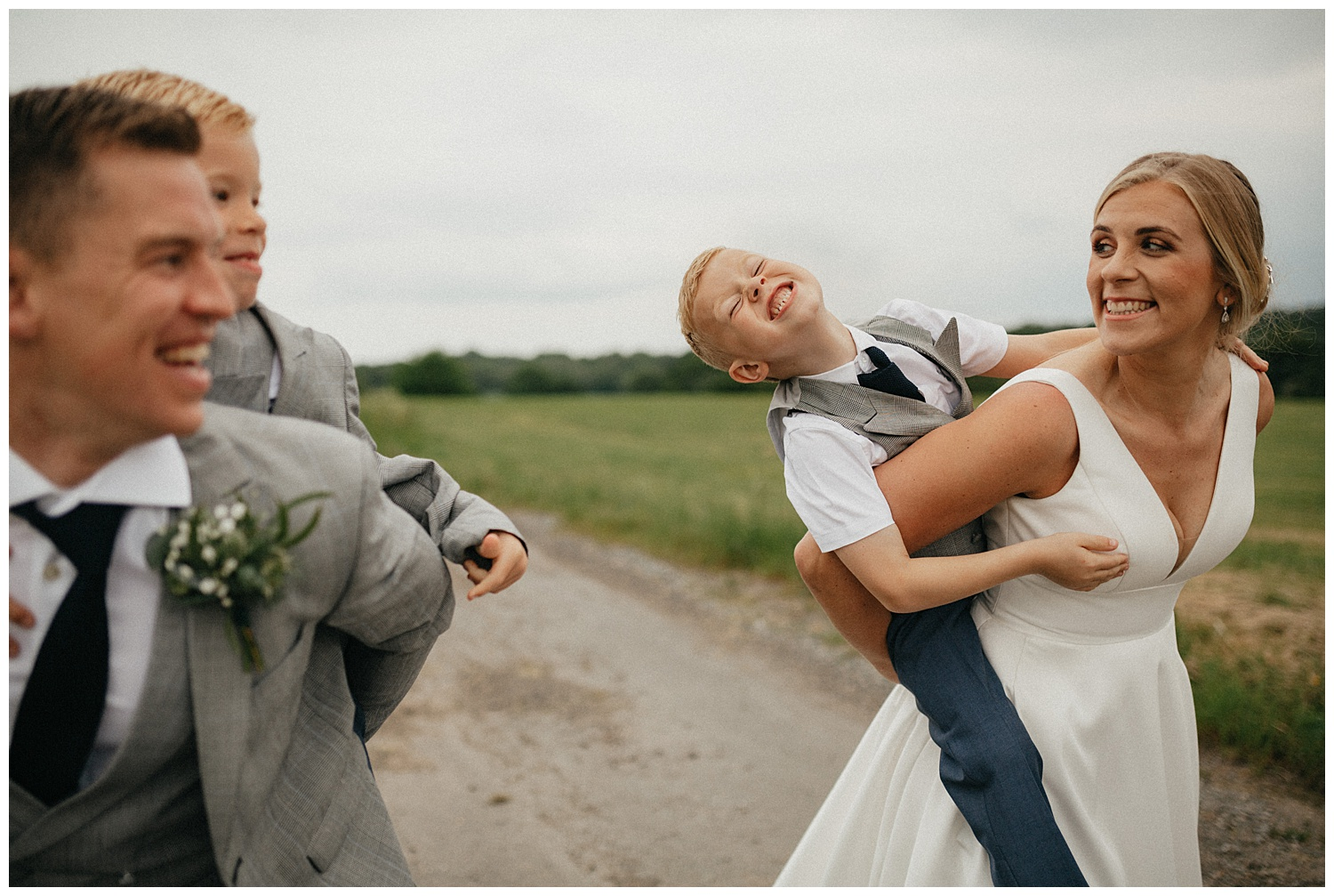 Weddings-at-Crondon-Park-bride-and-groom-carry-their-kids-and-laugh
