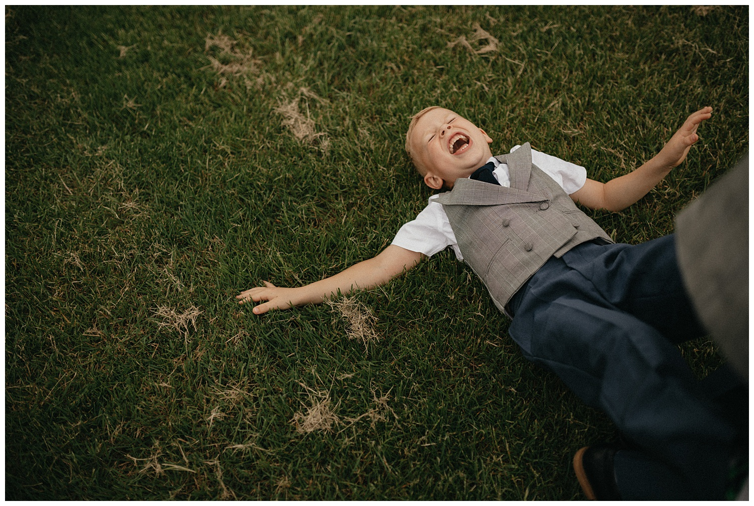Weddings-at-Crondon-Park-boy-laughs-on-the-grass